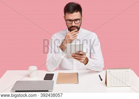 Indoor Shot Of Male Director Perfectionist Reads Financial News On Internet Website, Watches Promoti