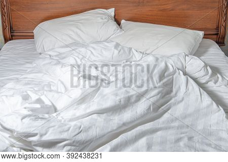 Unmade Bed With White Linens. Unmade Empty Bed. Close Up Unmade Bed Sheet In The Bedroom After Night