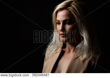 Young Beautiful Blond Glamorous Woman In Black Over Dark Background