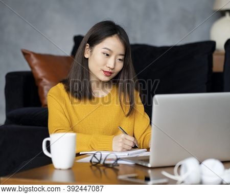 Asian Woman Working On Laptop At Home Or In Hotel. Young Lady In Bright Yellow Jumper