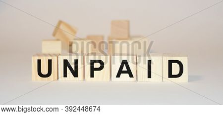 The Word Unpaid Is Written On Wooden Cubes.