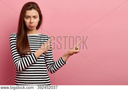 Distressed European Woman Purses Lips, Looks With Displeasure, Dressed In Striped Clothes, Shows Cop
