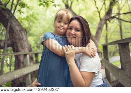 A Portrait Of Trisomie 21 Child Girl Outside With His Mother