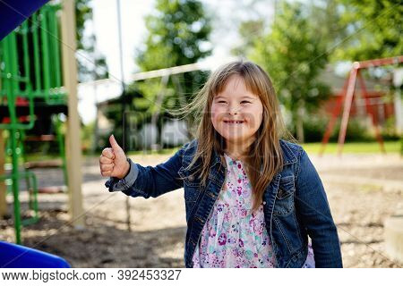 A Portrait Of Trisomie 21 Child Girl Outside Having Fun On A Park