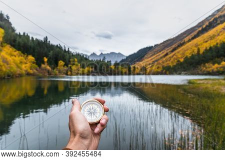 First-person View Of A Female Hand With A Compass On A Background Of A Beautiful Mountain Landscape.