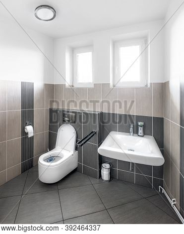 Small Modernly Furnished Toilet With A Sink And A Variety Of In-kind Accessories And Two Windows Lit