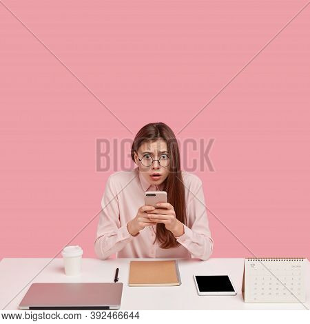 Photo Of Frustrated Perfectionist Holds Mobile Phone, Publishes New Post, Edits Photos In Social Net