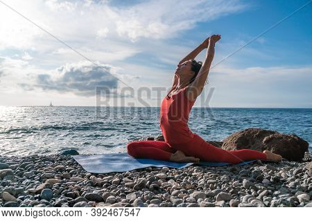 Selective Focus. Young Beautiful Caucasian Woman In A Red Suit Practicing Yoga, Fitness And Stretchi