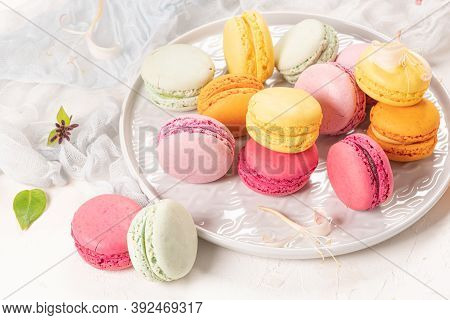 Colorful French Macaroon Cakes. Macaroons With Jasmine Flowers On White Table Background. Selective