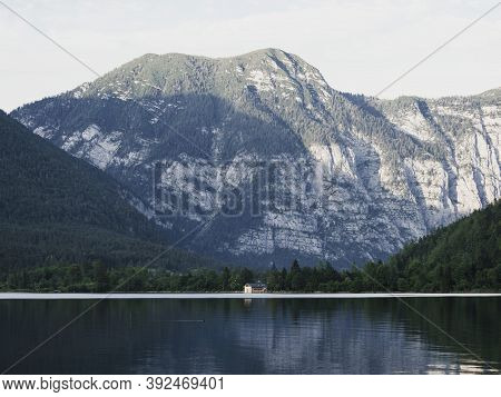 Boat House At Lake Hallstatt With Massive Mountain In Background