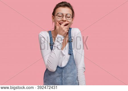 Delighted Young Caucasian Woman Covers Mouth From Laughter, Giggles At Something Positive, Wears Opt
