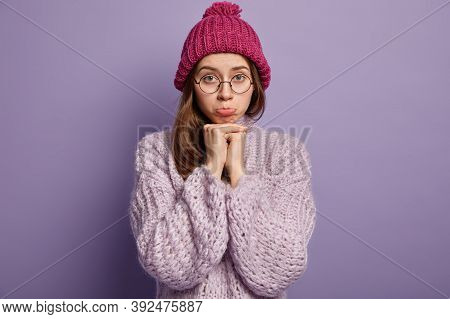 Photo Of Attractive Young Woman Purses Lips, Keeps Hands Under Chin, Wears Hat And Sweater, Feels De