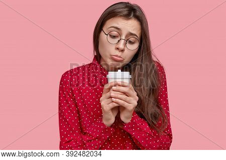 Lonely Dejected Woman Purses Lower Lip, Holds Disposable Cup Of Hot Drink, Feels Sad, Being In Low S