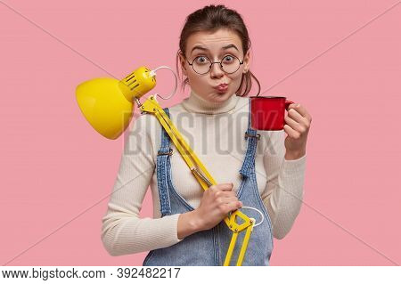 Shot Of Pretty Youngster Purses Lips, Carries Mug With Tea And Yellow Desk Lamp, Ready For Studying,