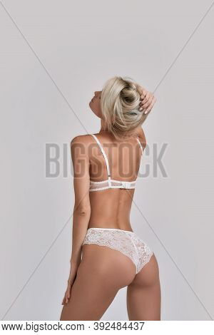 Young Sensual Woman With Perfect Body Wearing White Lingerie Looking Sexy While Posing Isolated Over