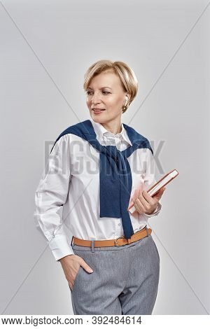 Portrait Of Elegant Middle Aged Caucasian Woman Wearing Business Attire Looking Aside, Holding Her N