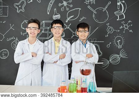 Group Of Happy Schoolchildren In Labcoats And Protective Goggles Folding Arms And Smiling At Camera