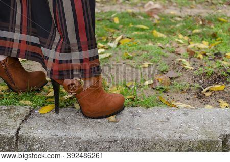 Woman In Long Skirt And  Brown High-heeled Boots Walks In Park. Suede Shoes With Decorative Flowers