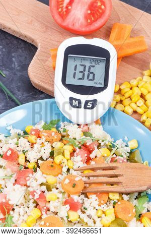 Glucose Meter For Checking Sugar Level And Fresh Salad With Vegetables And Couscous Groats. Light An