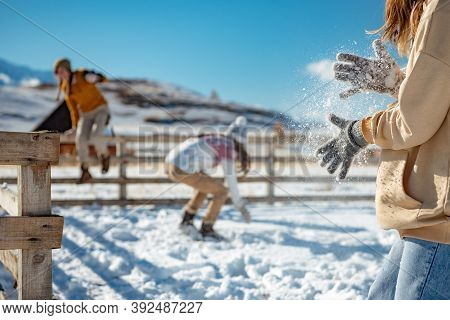 Three Girls Plays Snowballs In Mountains. Girl Shaking Off Snow From Hands