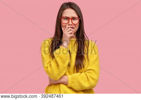 Photo Of Dejected Brunette Woman Cries Desperately, Has Grieved Facial Expression, Wears Yellow Jump