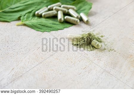 Selective Focus At Herbal Powder. With Blurred Herb Capsule With Herbal Leaf On Natural Wooden Backg