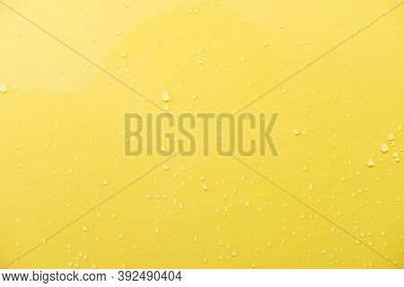 Close Up Shot Of Glossy Yellow Car Paint Surface. With Drop Of Water And Light Ambient. Background O