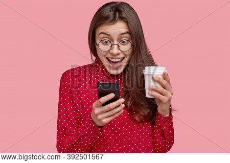 Photo Of Cheerful Young Woman Checks Social Networks, Plays Games On Phone, Browses Online Apps, Dri