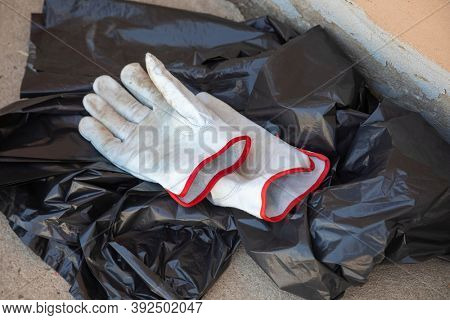 leather gloves and black garbage bag collecting the trash