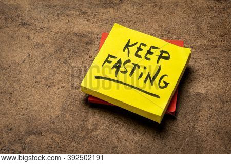 keep fasting reminder note on a brown textured bark paper, healthy lifestyle, intermittent fasting, diet and weight loss, time-restricted eating, daily eating window concept