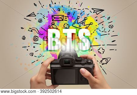Close-up of a hand holding digital camera with abstract drawing and BTS inscription
