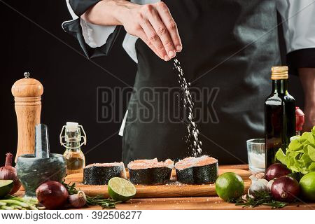 Chef Sprinkles Salt Onto Fish. Professional Cook Seasoning Salmon Steaks