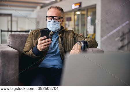 Man In A Face Mask Staring At His Gadget