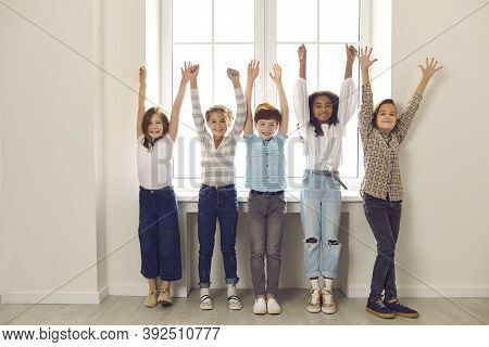 Group Of Diverse Children Of Classmates Stand With Raised Hands In The School Corridor.