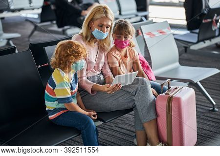 Family Watching Something On A Tablet In The Airport