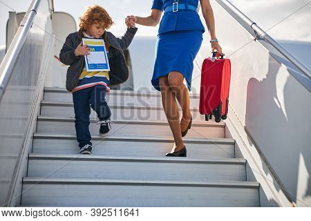 Unaccompanied Minor Descending From Boarding Stairs With A Stewardess