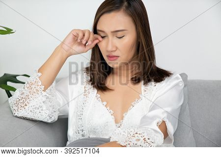 Asian Women In A Nightgown And Wear White Satin Robe Rubbing Her Eye Sitting On The Gray Sofa In The