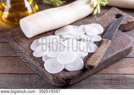 White Radish Sliced On Wooden Table. Daikon Radish