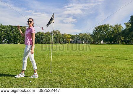 Joyous Golf Player Standing Near The Flagstick