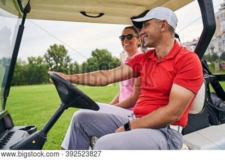 Smiling Man Giving A Ride To A Lady Golfer