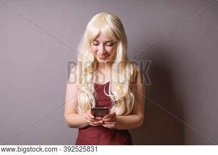 Happy Smiling Young Woman Looking Down At Text Message On Her Smartphone - Mobile Communication And
