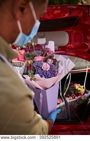 Floral Specialist Loading A Posy Into A Luggage Boot