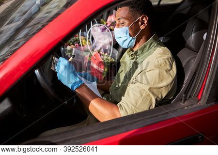 Floral Artist Writing Information In A Car With Open Window