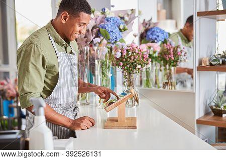 Joyful Young Man Working As Cashier At Florist