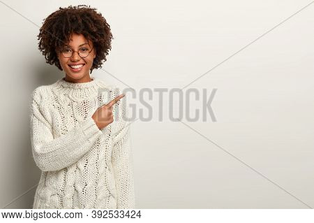 Visit This. Cheerful Delighted Woman Points Right With Fore Finger, Shows Copy Space For Your Promot