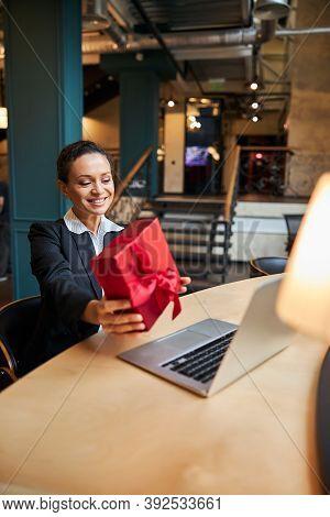 Pleased Brunette Office Worker Demonstrating Gift Box