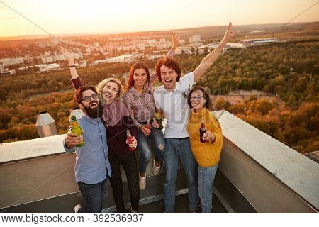 High Angle Of Group Of Excited Laughing Young Friends In Casual Outfits Holding Bottles Of Beer And
