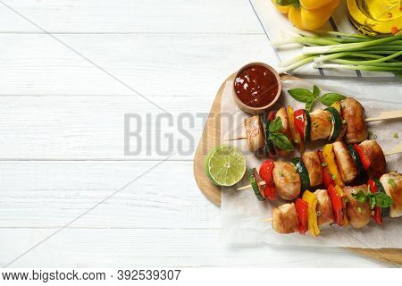 Delicious Chicken Shish Kebabs With Vegetables And Ketchup On White Wooden Table, Flat Lay. Space Fo