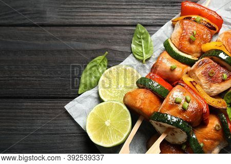 Delicious Chicken Shish Kebabs With Vegetables And Lime On Black Wooden Table, Top View. Space For T