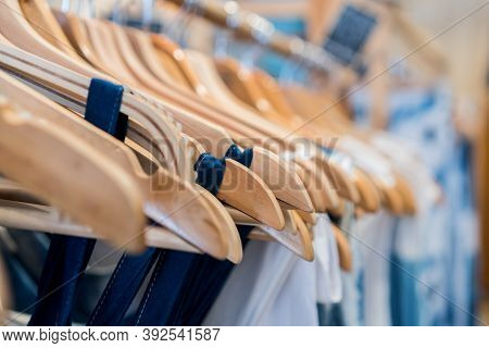 Ladies Clothes On Wooden Hangers In Shelf Fashion For Sale In Shopfront Store, Retail Background.